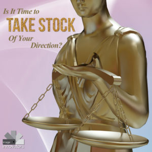 gold statiue of woman with scales under text Is it time to take stock of your direction